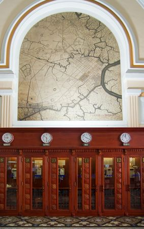 Old, wooden phone booths at the post office in Ho Chi Minh City, with an old Saigon map on the wall. photo