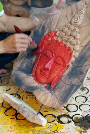 Hand painting the face of a Buddha image with red paint. Motion blur on the painting hand.