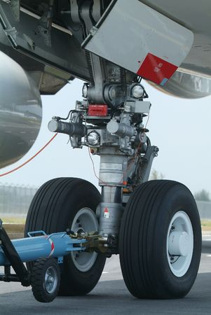 Nose wheel (front landing gear) of very large, wide-body airplane being towed at an airport.