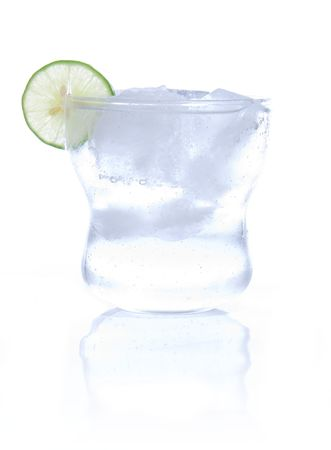 highkey: Glass of soda water with ice cubes and a slice of lime. High-key photo, isolated on white with reflection in the foreground.