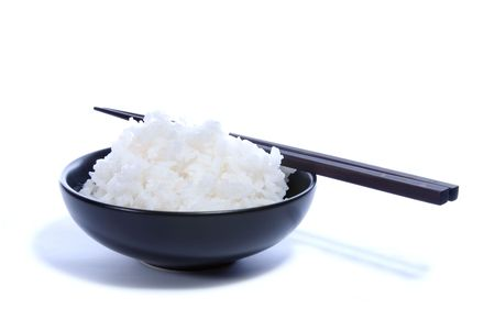 Black bowl with white rice and chop sticks isolated on white. Stock Photo