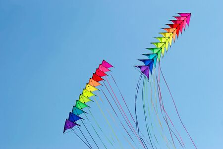 flying a kite: Two stacks of 12 stunt kites in rainbow colours on a blue sky background Stock Photo