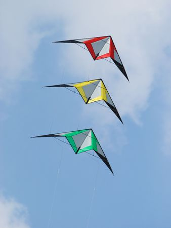 Stack of three stunt kites in the colours red, yellow and green. Stock Photo