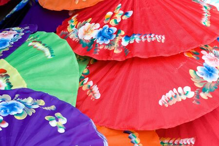 Hand painted cotton umbrellas in assorted colours with flower motives at a handicraft festival in Bo Sang, Chiang Mai, Thailand. Shallow depth of field with the nearest umbrellas in focus. photo