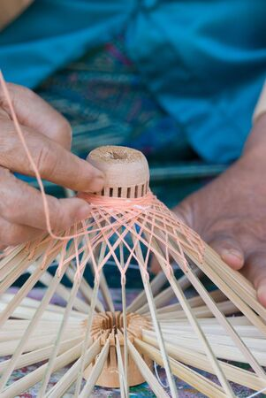 Hand of an elderly woman making the wooden frame for a traditional Thai umbrella in the umbrella village Bo Sang, Chiang Mai, Thailand.  photo