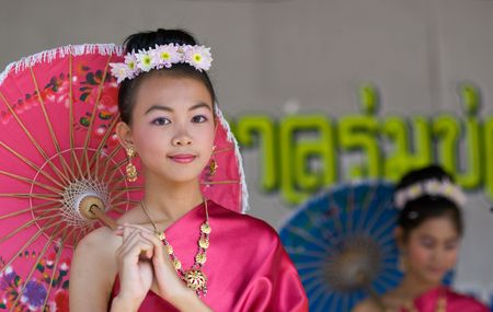 CHIANG MAI, THAILAND - JANUARY 15: Girls performing in national costumes during the annual Umbrella festival in Chiang Mai, Thailand on January 15, 2010. The festival is held in Bo Sang, where traditional umbrellas have been made for more than 100 years.