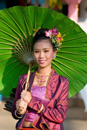 handicrafts: CHIANG MAI, THAILAND - JANUARY 15: Woman in traditional costume during the annual Umbrella festival in Bo Sang, Chiang Mai, Thailand on January 15, 2010, where traditional umbrellas have been made for more than 100 years.