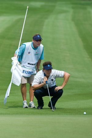 BANGKOK, THAILAND - JANUARY 8: Spanish golf player Pablo Martin and his caddie preparing a put at the Royal Trophy tournament, Asia vs Europe, at Amata Spring, Bangkok, Thailand on January 8, 2010. Editorial