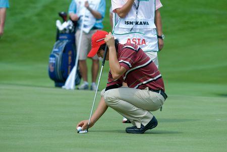 BANGKOK, THAILAND - JANUARY 8: Japanese golf player Ryo Ishikawa preparing a put at the Royal Trophy tournament, Asia vs Europe, at Amata Spring, Bangkok, Thailand on January 8, 2010.