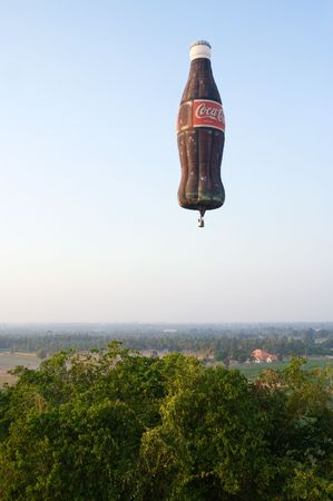 PATTAYA, THAILAND - DECEMBER 12: Hot-air balloon shaped as a Coca-Cola bottle flying during Pattaya International Balloon Fiesta 2009 at Pattaya, Thailand on December 10-13, 2009.  Editorial