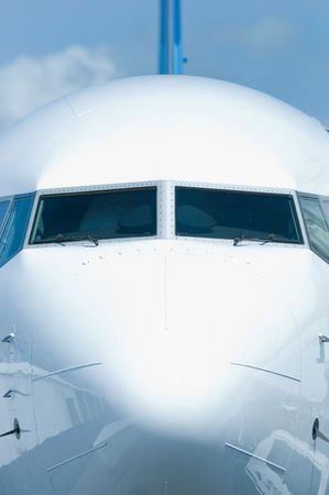 Front view of white passenger airplane with ground equipment reflected in the hull. Stock Photo
