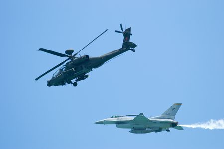 SINGAPORE - FEBRUARY 3: Singapore Air Force F-16 fighter aircraft and AH-64 Apache attack helicopter at Singapore Airshow 2010 at Changi Exhibition Centre, Singapore on January 15, 2010.