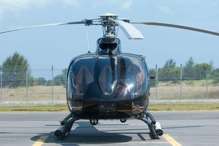 heliport: Front view of black helicopter at an airport
