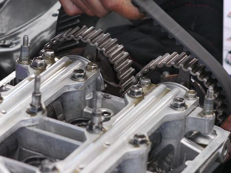 Camshaft timing belt being replaced on car engine with double overhead cams, DOHC. Shallow depth of field with the sprockets in focus.