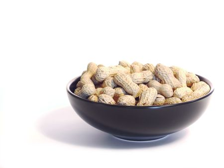 earthnut: Black bowl with unshelled peanuts, isolated on white. Stock Photo