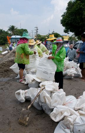 unusually: AYUTTAYA - OCTOBER 20: Women making sandbags to prevent flooding after unusually heavy monsoon rain on October 20, 2010 in Ayuttaya, Thailand.  Editorial