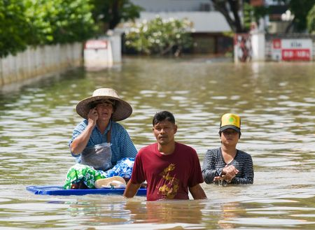 NAKHON RATCHASIMA - OCTOBER 24: People floating their belongings while wading through deep water during the monsoon flooding of October 24, 2010 in Nakhon Ratchasima, Thailand. Editorial