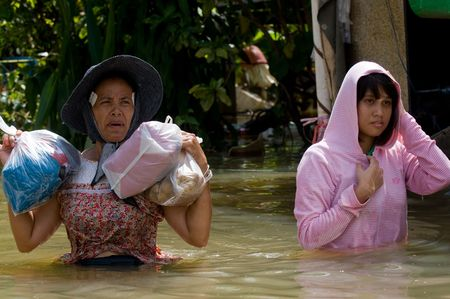 wade: NAKHON RATCHASIMA - OCTOBER 24: Two women wading through deep water with bags of food during the monsoon flooding of October 24, 2010 in Nakhon Ratchasima, Thailand. Editorial