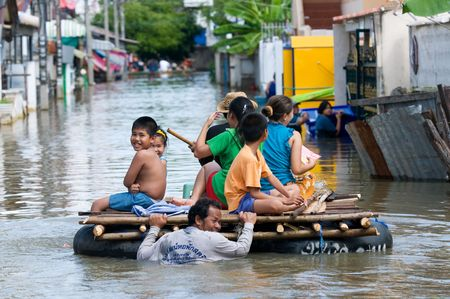 katastrof: NAKHON RATCHASIMA - OCTOBER 24: Villagers going home on an improvised raft during the monsoon flooding of October 24, 2010 in Nakhon Ratchasima, Thailand. Redaktionell