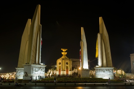 democracy monument: BANGKOK - DECEMBER 5: The Democracy Monument on Rachadamnoen road decorated with flags for the celebration of the 83rd birthday of HM King Bhumibol Adulyadej on December 5, 2010 in Bangkok, Thailand.