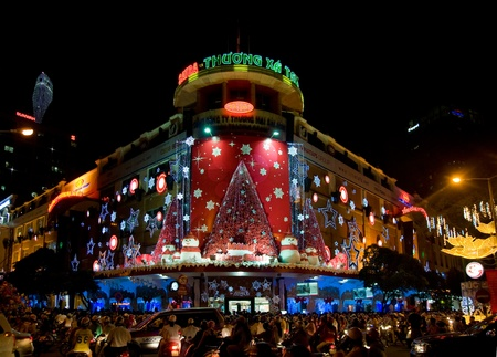 HO CHI MINH CITY - DECEMBER 22: Decorated department store and shoppers in the street on December 22, 2010 in Ho Chi Minh City.