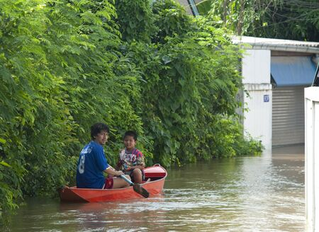 ayuttaya: AYUTTAYA, THAILAND - OCTOBER 5: Father and son paddling down a flooded street during the monsoon season in Ayuttaya, Thailand on October 5, 2011.