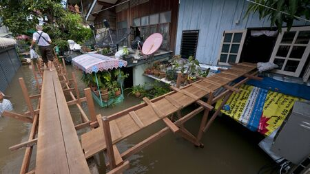 AYUTTAYA, THAILAND - OCTOBER 5: Temporary pedestrian bridge and entrance to house through second floor window during monsoon season in Ayuttaya, Thailand on October 5, 2011. Stock Photo - 10781247