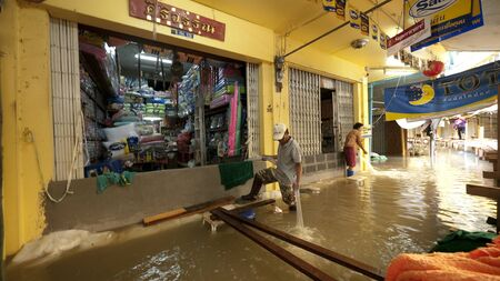 ayuttaya: AYUTTAYA, THAILAND - OCTOBER 5: Shop owners pumping water from their shops during the monsoon season in Ayuttaya, Thailand on October 5, 2011.