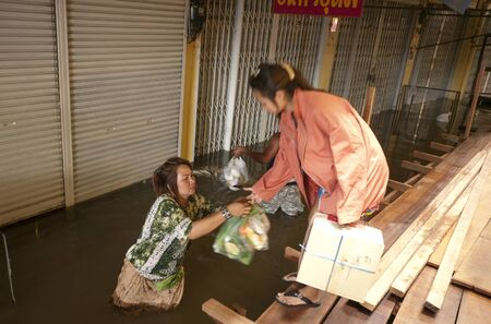 ayuttaya: AYUTTAYA, THAILAND - OCTOBER 5: Shop owners bringing supplies to their shops during the monsoon season in Ayuttaya, Thailand on October 5, 2011. Editorial