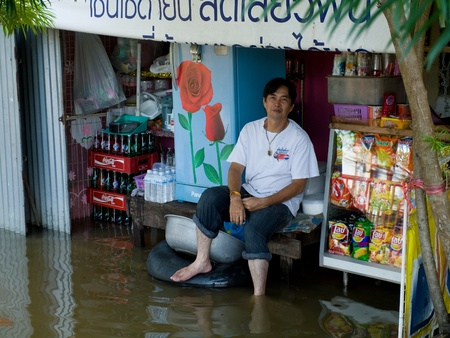 AYUTTAYA, THAILAND - OCTOBER 5: Flooded shop and shop owner during the monsoon season in Ayuttaya, Thailand on October 5, 2011. Stock Photo - 10781230