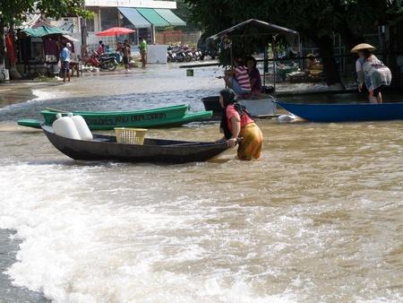 ayuttaya: AYUTTAYA, THAILAND - OCTOBER 5: Muslim woman transporting supplies in a small boat during the monsoon season in Ayuttaya, Thailand on October 5, 2011.