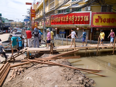 AYUTTAYA, THAILAND - OCTOBER 5: Temporary bridge made from teakwood in a flooded city center during the monsoon season in Ayuttaya, Thailand on October 5, 2011. Stock Photo - 10781246