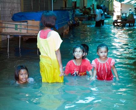 ayuttaya: AYUTTAYA, THAILAND - OCTOBER 5: Children at a flooded shopping mall during the monsoon season in Ayuttaya, Thailand on October 5, 2011. Editorial