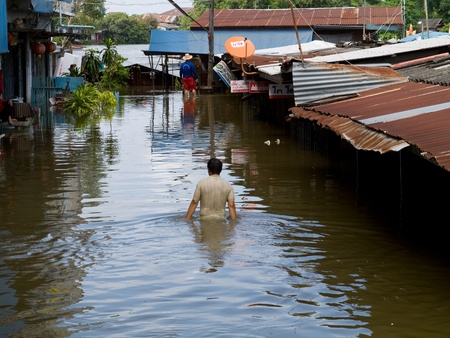 AYUTTAYA, THAILAND - OCTOBER 5: Man wading through a flooded street during the monsoon season in Ayuttaya, Thailand on October 5, 2011.