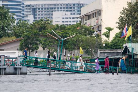 chao praya: BANGKOK, THAILAND - OCTOBER 17: Ferry passenger exiting a flooded pier at the flooding Chao Praya River during the worst flooding in decades in Bangkok, Thailand on October 17, 2011.