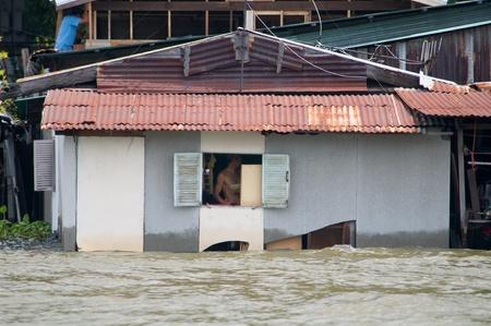 praya: BANGKOK, THAILAND - OCTOBER 17: Flooded community along Chao Praya River during the worst flooding in decades in Bangkok, Thailand on October 17, 2011.
