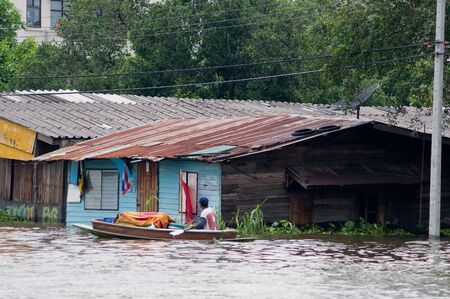 BANGKOK, THAILAND - OCTOBER 17: Man paddling through a flooded community along a canal during the worst flooding in decades in Bangkok, Thailand on October 17, 2011.