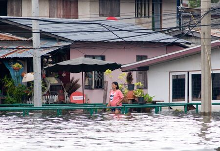 BANGKOK, THAILAND - OCTOBER 17: Woman walking througha flooded community along Chao Praya River during the worst flooding in decades in Bangkok, Thailand on October 17, 2011.