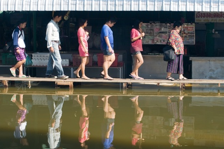 worst: BANGKOK, THAILAND - OCTOBER 25: People walking down a street on a temporary bridge during the worst flooding in decades in Bangkok, Thailand on October 25, 2011.