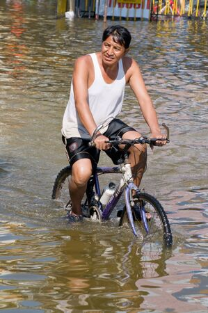 decades: BANGKOK, THAILAND - OCTOBER 25: Man navigating a bicycle through the water during the worst flooding in decades in Bangkok, Thailand on October 25, 2011.