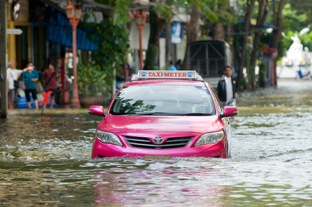 inundated: BANGKOK, THAILAND - OCTOBER 29: Pink taxi navigating a street during the worst flooding in decades in Bangkok, Thailand on October 29, 2011.