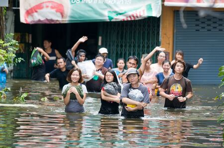 decades: BANGKOK, THAILAND - OCTOBER 29: Group of people wading to escape the worst flooding in decades in Bangkok, Thailand on October 29, 2011. Editorial