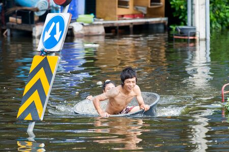 transported: BANGKOK, THAILAND - OCTOBER 29: Man being transported in a tub during the worst flooding in decades in Bangkok, Thailand on October 29, 2011. Editorial
