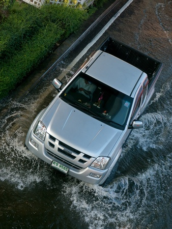 BANGKOK, THAILAND - NOVEMBER 6: Pickup truck driving down a flooded street during the worst flooding in decades in Bangkok, Thailand on November 6, 2011.