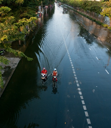 decades: BANGKOK, THAILAND - NOVEMBER 6: Two motorcycle taxis driving down a flooded street during the worst flooding in decades in Bangkok, Thailand on November 6, 2011. Editorial