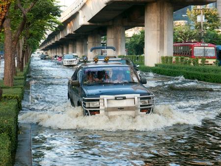 decades: BANGKOK, THAILAND - NOVEMBER 6: Cars and trucks driving down a flooded street during the worst flooding in decades in Bangkok, Thailand on November 6, 2011.