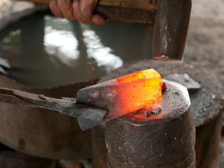 forge: Blacksmith using a heavy hammer to forge an ax