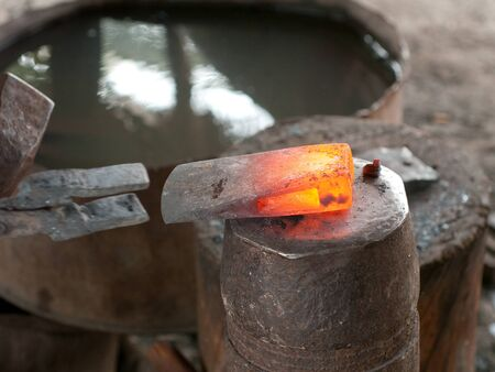 skillful: Red hot head of ax at a blacksmiths workshop in the final stage of production