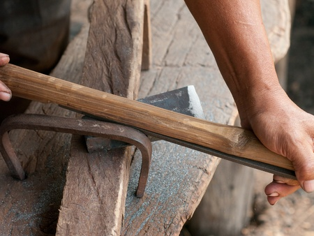 skillful: Blacksmith sharpening an ax using a file mounted on a shaft. Stock Photo