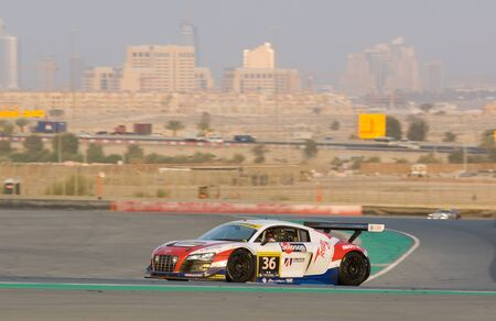 gt3: DUBAI - JANUARY 14: Car 36, an Audi R8 GT3 LMS with Dubai City in the background, during the 2012 Dunlop 24 Hour Race at Dubai Autodrome on January 14, 2012.